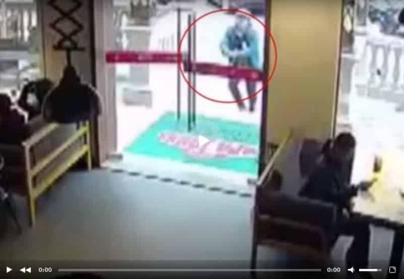 В Китае курьер случайно разбил стеклянную дверь ресторана и остался стоять с металлической ручкой