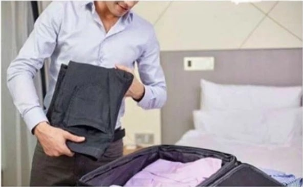 мужчина пакует вещи в чемодан