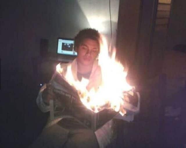 парень с горящей газетой