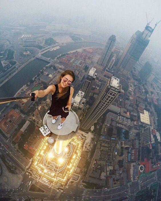 девушка на краю небоскреба делает селфи