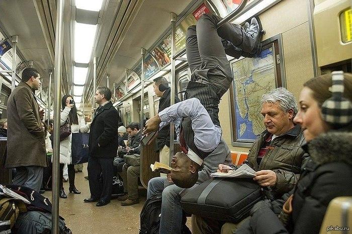 мужчина висит вниз головой в вагоне метро