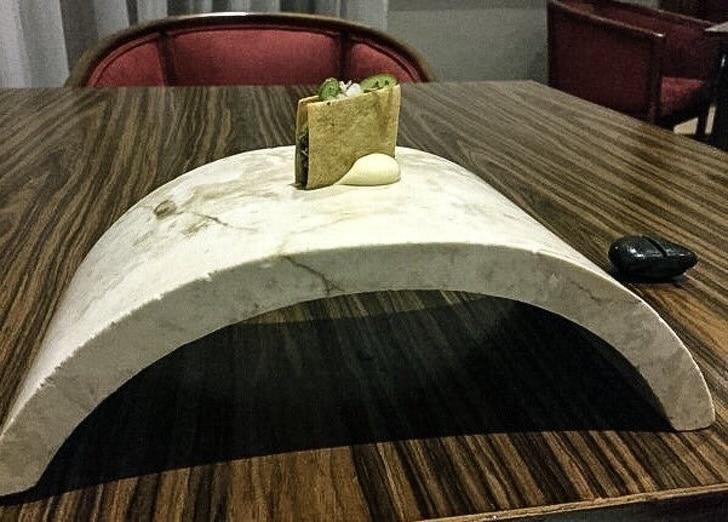 подача блюда на изогнутой тарелке