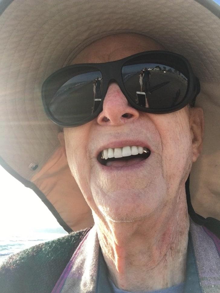 старик делает селфи на пляже