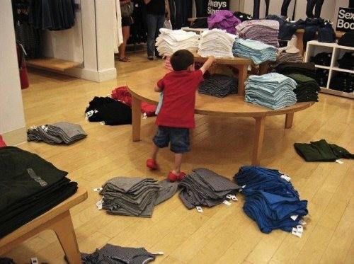 мальчик раскидывает вещи в магазине одежды