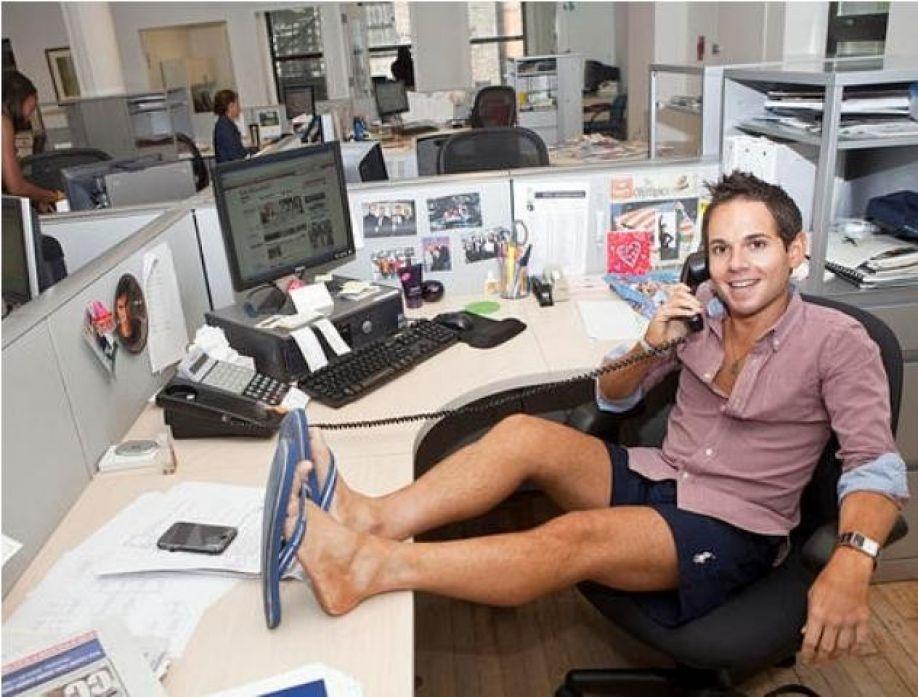 парень в рубашке, шортах и шлепанцах в офисе