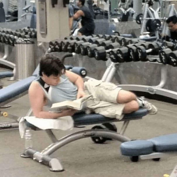 парень читает книгу в тренажерном зале
