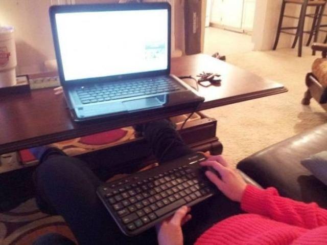 человек сидит перед ноутбуком с клавиатурой