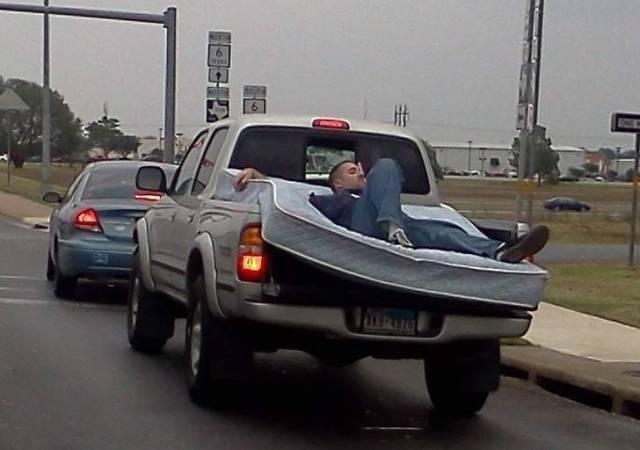 мужчина на матрасе едет на машине