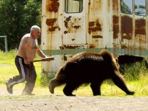 мужчина прогоняет медведя