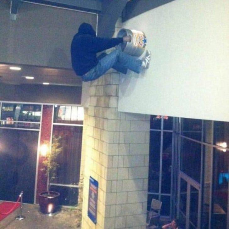 мужчина висит на стене
