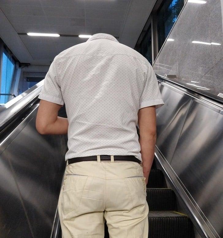 парень без головы на эскалаторе
