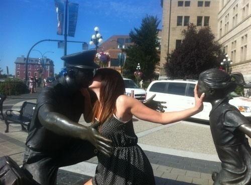 девушка целует скульптуру