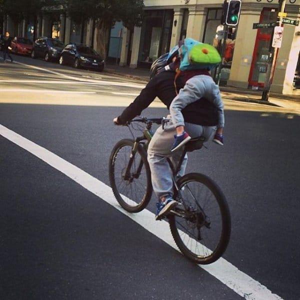 велосипедист с ребенком на спине