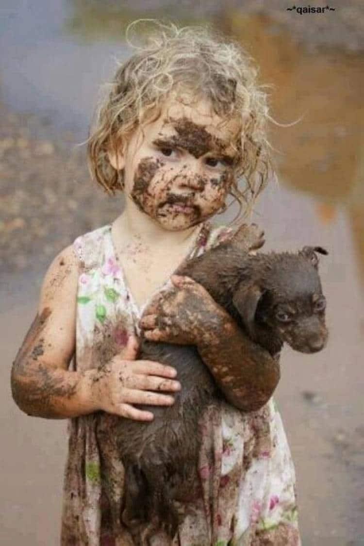 грязная девочка держит щенка