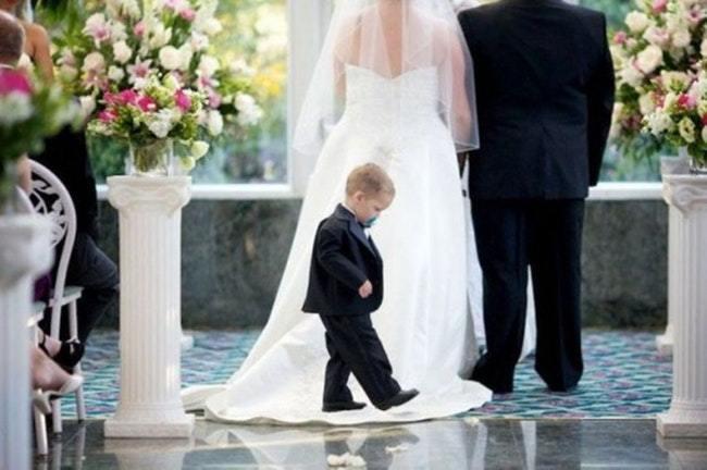мальчик стоит на платье невесты