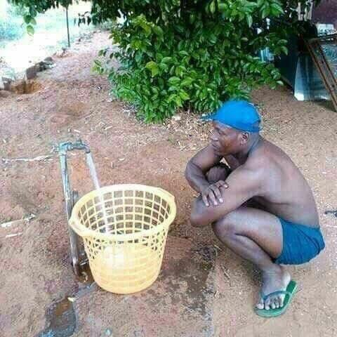 чернокожий мужчина набирает воду в ведро
