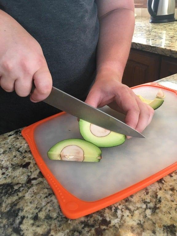 парень режет авокадо
