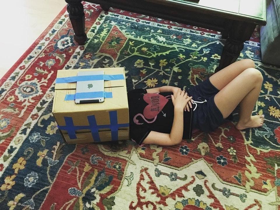 девушка лежит на ковре с коробкой на голове