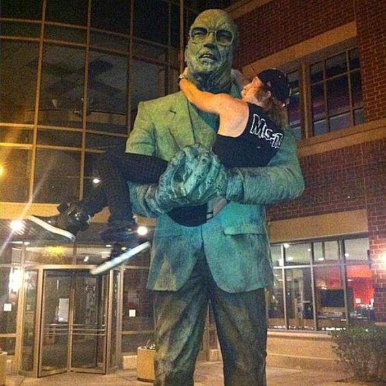 парень на руках у памятника