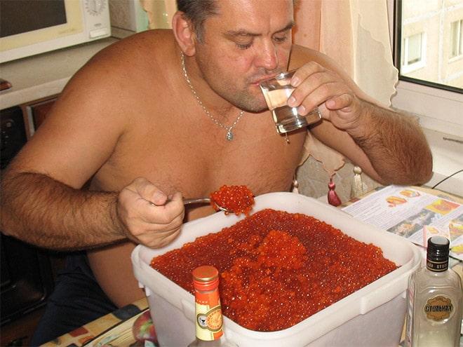 мужчина пьет водку и ест икру