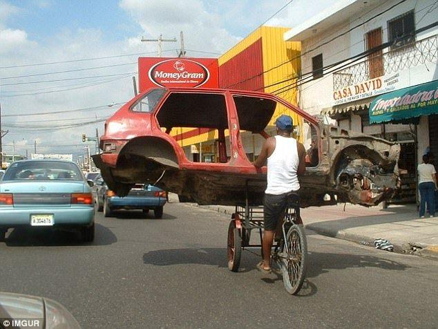 мужчина на велосипеде везет авто