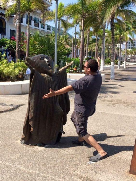 мужчина обнимается с памятником
