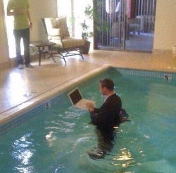 мужчина с ноутбуком в бассейне