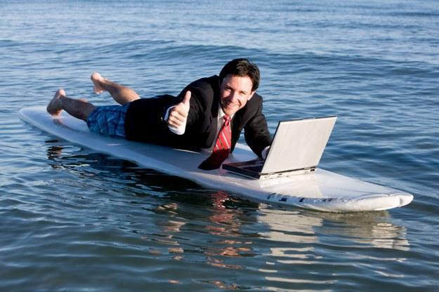 мужчина с ноутбуком на доске для серфинга
