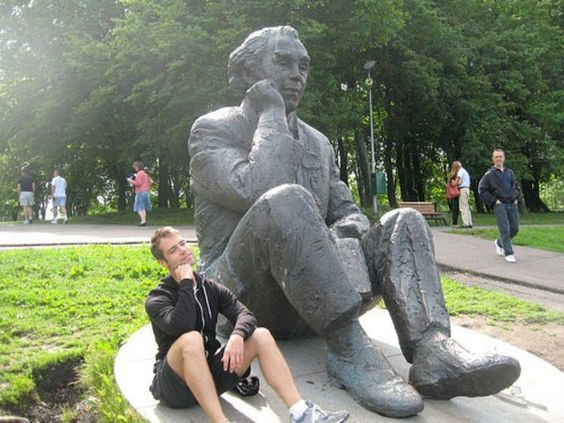 парень сидит рядом со статуей