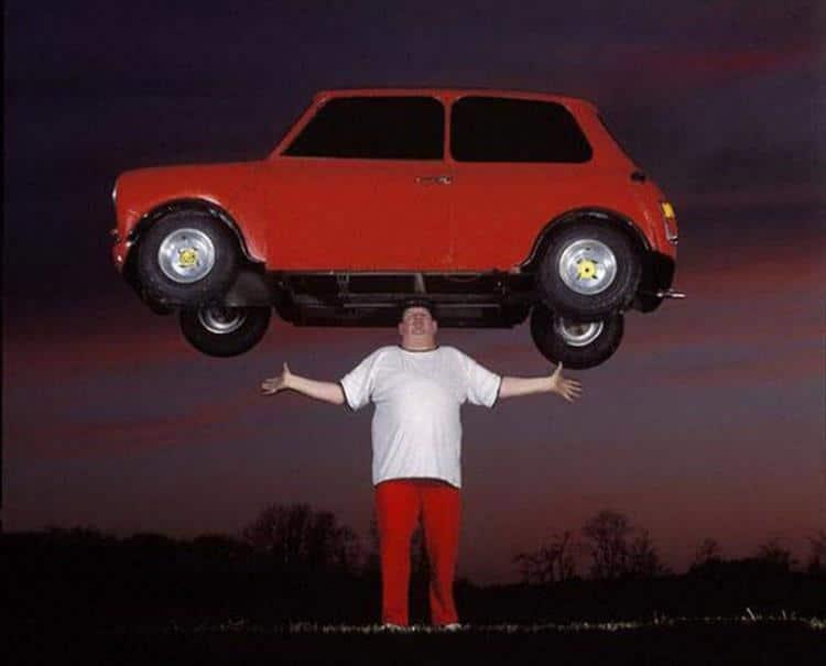 мужчина держит на голове автомобиль