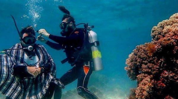 аквалангист стрижет парня под водой