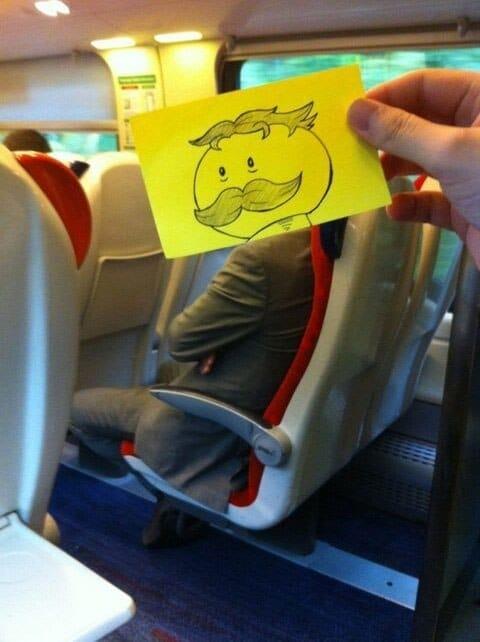 мужчина в поезде с нарисованной головой