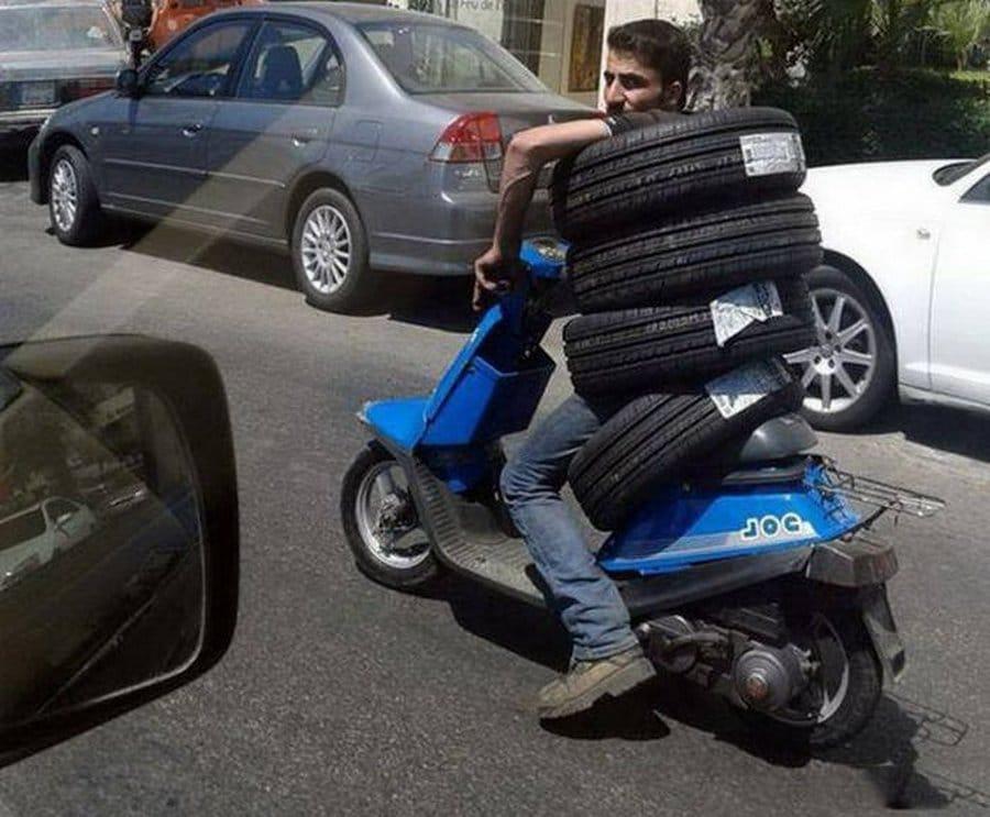 парень с покрышками на мотороллере