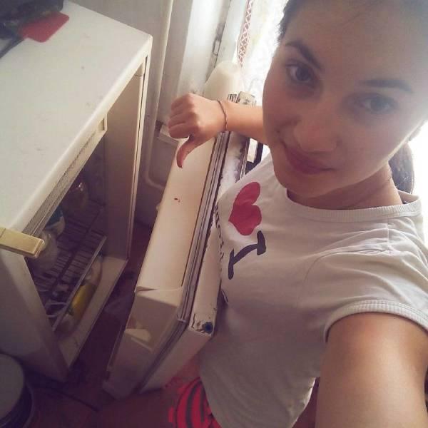 девушка делает селфи на фоне поломанного холодильника
