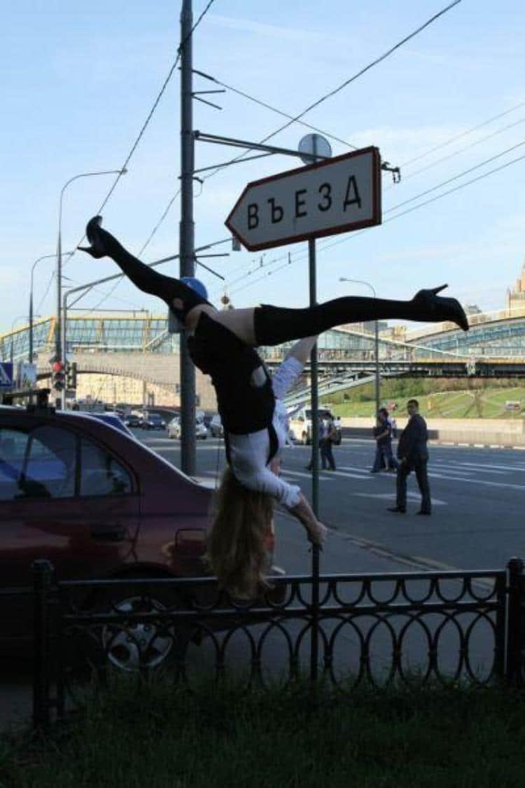 девушка висит на дорожном знаке