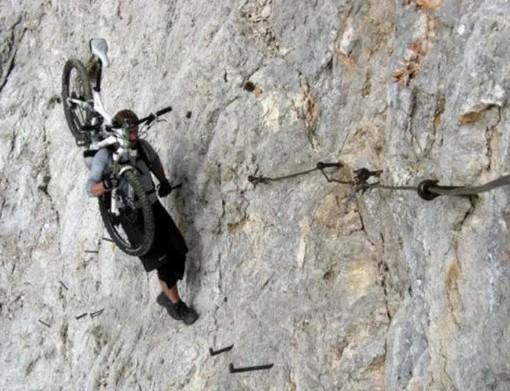 мужчина с велосипедом в горах
