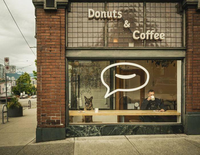 мужчина-полицейский пьет кофе в кафе рядом за столом сидит собака