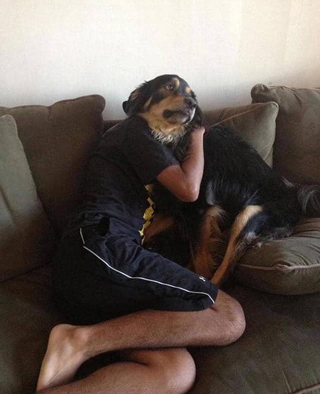 парень обнимает собаку на диване