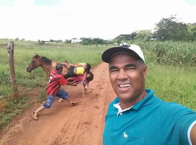 мужчина делает селфи на фоне лошади
