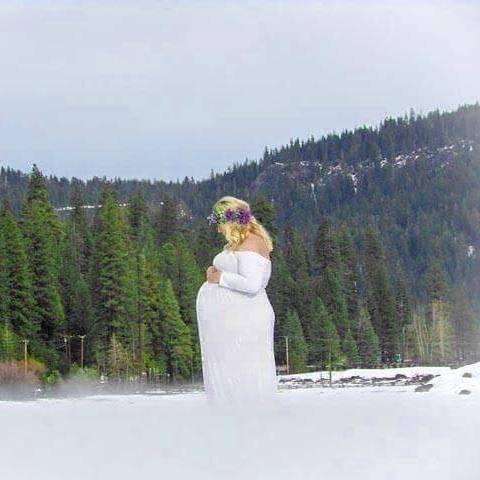 беременная девушка на фоне гор зимой