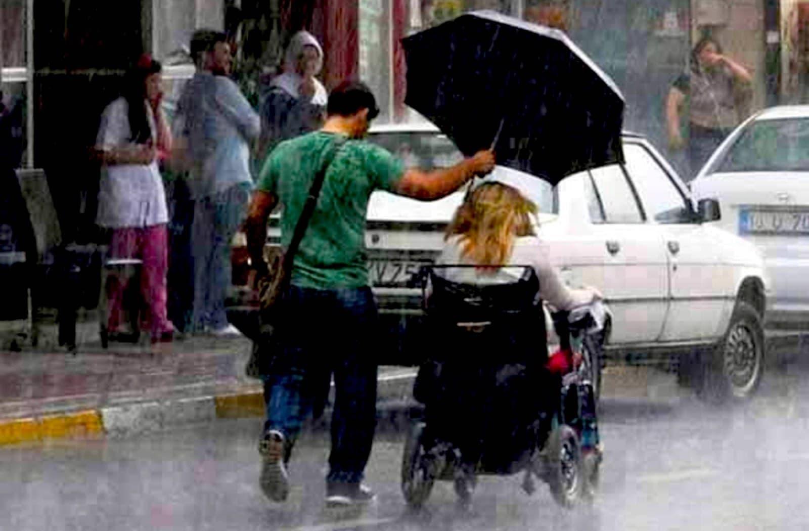 мужчина с зонтом и женщина на коляске