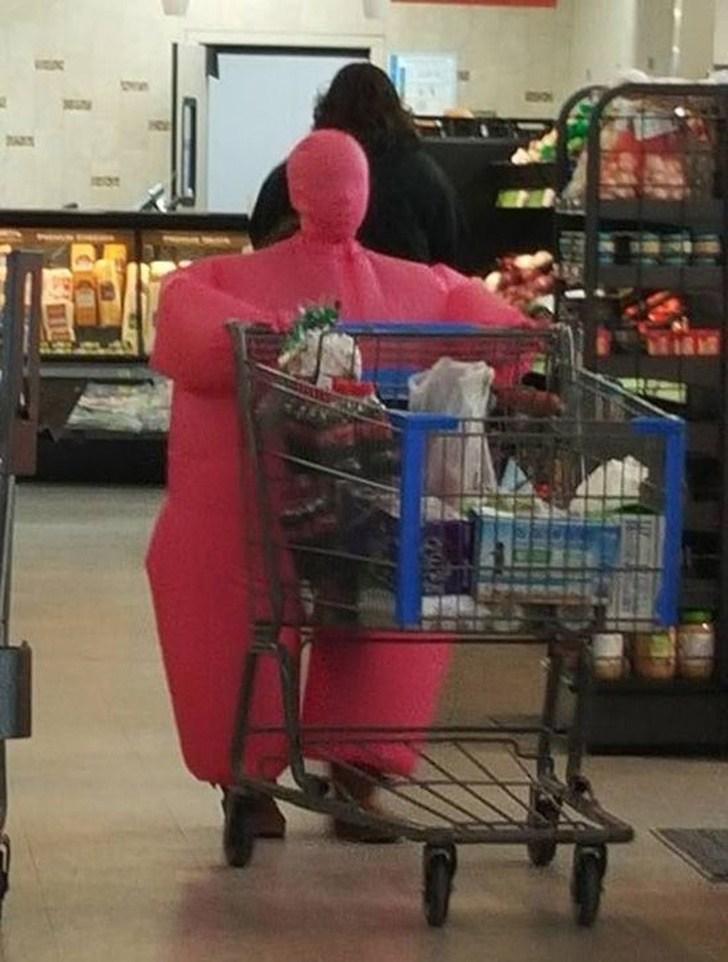 человек в розовом костюме с тележкой