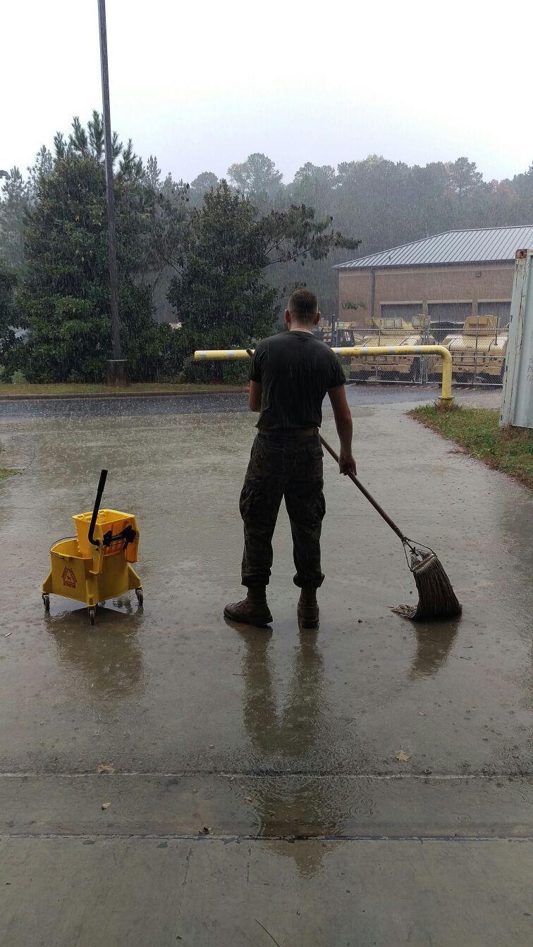 парень моет асфальт под дождем