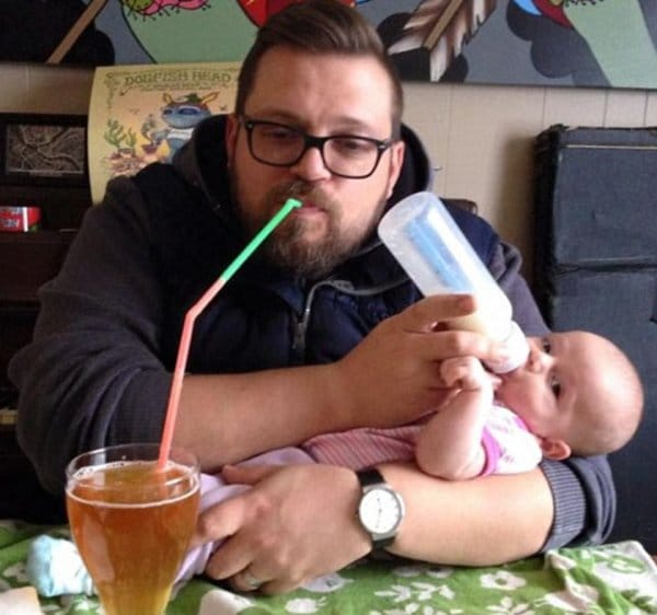 папа кормит ребенка с бутылочки и пьет пиво