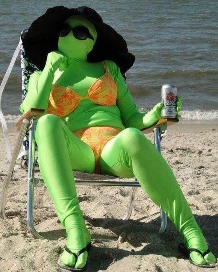женщина в зеленом костюме на пляже