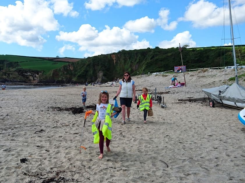 дети и мама собирают мусор на пляже