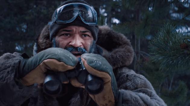 мужчина зимой в лесу держит бинокль