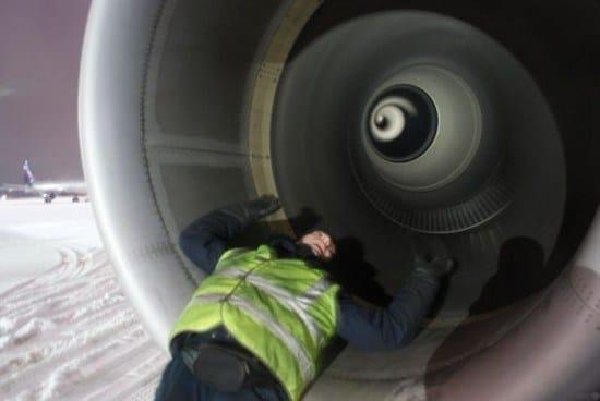 работник аэропорта лежит в турбине самолета