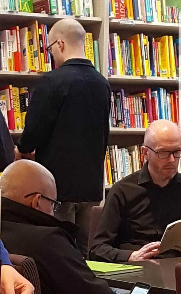 три бритоголовых мужчины в библиотеке
