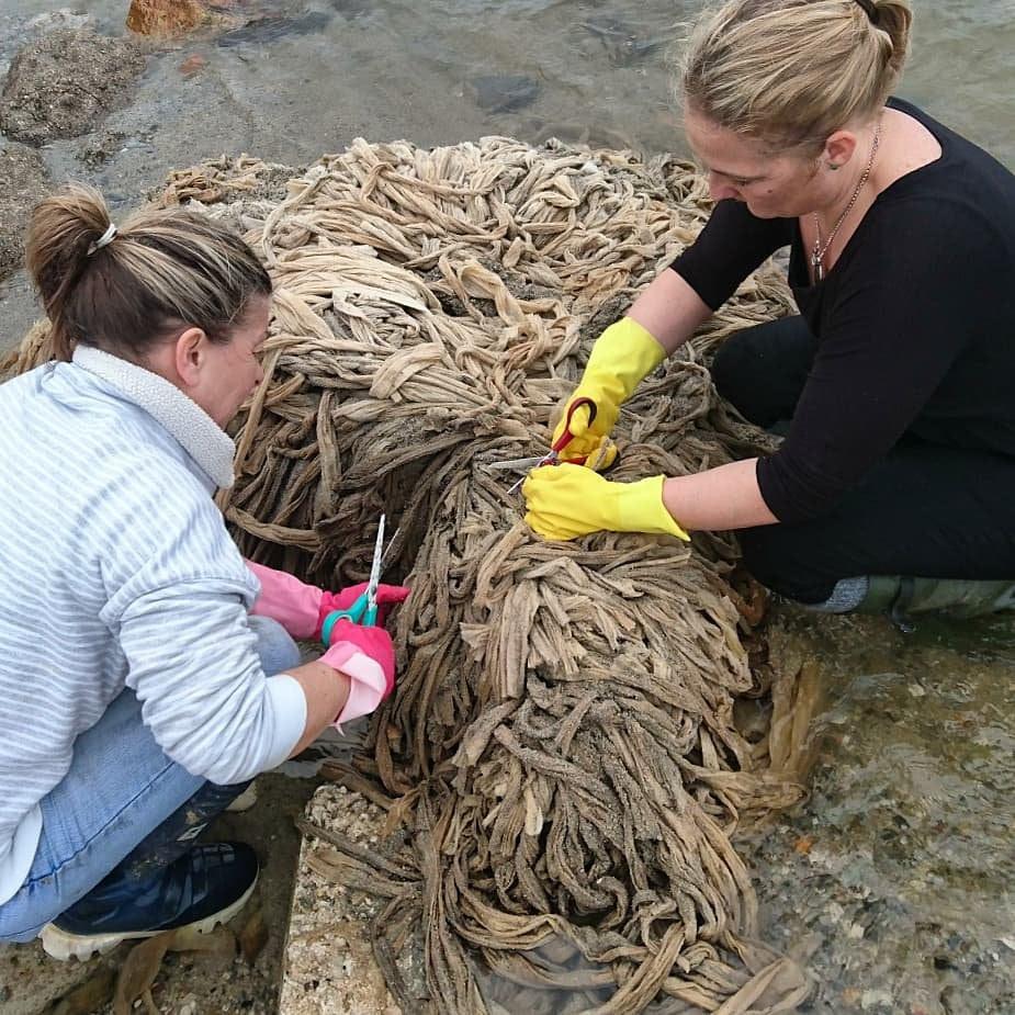 женщины разрезают тюк из материала грязного